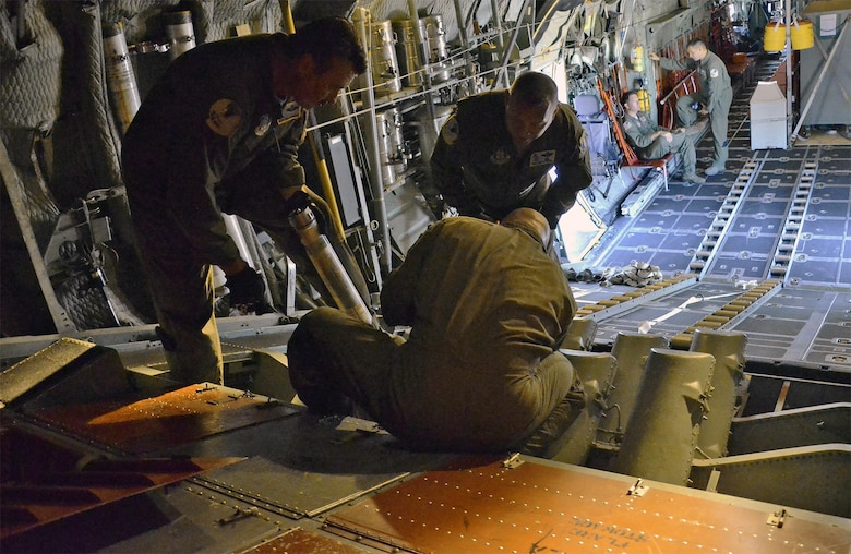 PATRICK AIR FORCE BASE, Fla. -- Air Force Reserve aircrew members load cannisters of sea dye into the flare launcher system of an HC-130P/N King aircraft prior to launching a search-and-rescue mission. The dye, which spreads into a large, bright flourescent green patch in seawater, is used to mark the location of a survivor during a search operation. The reservists are members of the 920th Rescue Wing, the Air Force Reserve's only rescue unit. (U.S. Air Force photo/Master Sgt. Paul Flipse)