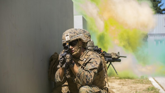 U.S. and ROK Marines breach a building under smoke concealment during Korean Marine Exchange Program 15-12 at Gunha-Rhi, Gimpo, Republic of Korea, Sept. 17, 2015. KMEP 15-12 is a bilateral training exercise that enhances the ROK and U.S. alliance, promotes stability on the Korean Peninsula and strengthens ROK and U.S. military capabilities and interoperability. The ROK Marines are with 1st Company, 11th Battalion, 1st Regiment, 2nd Marine Division. The U.S. Marines are with Fox Company, 2nd Battalion, 3rd Marine Regiment, currently assigned to 4th Marine Regiment, 3rd Marine Division, III Marine Expeditionary Force under the unit deployment program. (U.S. Marine Corps photo by Cpl. Tyler S. Giguere/ Released)