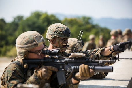 U.S. Marine 1st Lt. Matt Shibata, center, directs gunfire during Korean Marine Exchange Program 15-12 at Rodriguez Landing Zone, Republic of Korea, Sept. 25, 2015. Alongside their ROK counterparts, the Marines took over a fortified enemy hill to provide security for other Marines to press forward. KMEP 15-12 is a bilateral training exercise that enhances the ROK and U.S. alliance, promotes stability on the Korean Peninsula and strengthens ROK and U.S. military capabilities and interoperability. Shibata, from Honolulu, Hawaii, is with Fox Company, 2nd Battalion, 3rd Marine Regiment, currently assigned to 4th Marine Regiment, 3rd Marine Division, III Marine Expeditionary Force under the unit deployment program.
