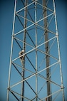 Senior Airman James Brown, 57th Operations Support Squadron airfield systems technician, ascends a ground-to-air radio tower at the Airfield Systems Maintenance compound on Nellis Air Force Base, Nev., Oct. 6, 2015. Airfield systems specialists must periodically preform preventative maintenance inspections on ground-to-air radio towers, which stand as tall as 180 feet. (U.S. Air Force photo by Staff Sgt. Siuta B. Ika)