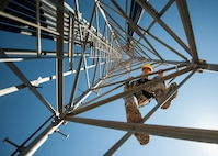 Senior Airman James Vrtis, 57th Operations Support Squadron airfield systems technician, descends a ground-to-air radio tower at the Airfield Systems Maintenance compound on Nellis Air Force Base, Nev., Oct. 6, 2015. Airfield systems specialists must periodically preform preventative maintenance inspections on ground-to-air radio towers, which stand as tall as 180 feet. (U.S. Air Force photo by Staff Sgt. Siuta B. Ika)