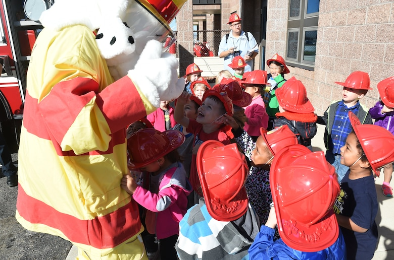 Sparky the Fire Dog greets children from the Crested Butte Child Development Center Oct. 7, 2015, on Buckley Air Force Base, Colo. Sparky was part of a visit from the Buckley Fire Department to both CDCs on base to spread the word about Fire Prevention Week. The fire department also brought fire trucks for the children to look at, along with plastic fire helmets and coloring books for them to take home. (U.S. Air Force photo by Airman 1st Class Samantha Meadors/Released)
