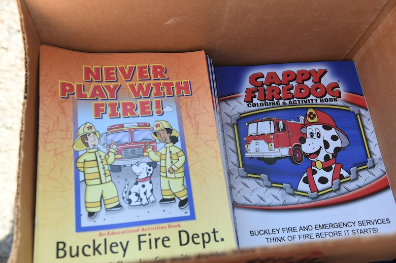 Coloring books were given to children from the Crested Butte Child Development Center during a visit by the Buckley Fire Department Oct. 7, 2015, on Buckley Air Force Base, Colo. The fire department visited both CDCs on base to spread the word about Fire Prevention Week. For the visit, the children got to meet Sparky the Fire Dog, look at fire trucks, and take home coloring books and plastic fire helmets. (U.S. Air Force photo by Airman 1st Class Samantha Meadors/Released)