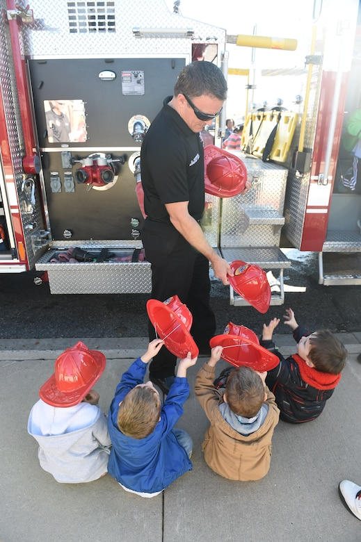 David Herman, Buckley Fire Department assistant fire chief, hands children from the Crested Butte Child Development Center plastic fire helmets Oct. 7, 2015, on Buckley Air Force Base, Colo. The fire department visited both CDCs on base to spread the word about Fire Prevention Week. For the visit, the children got to meet Sparky the Fire Dog, look at fire trucks, and take home coloring books. (U.S. Air Force photo by Airman 1st Class Samantha Meadors/Released)