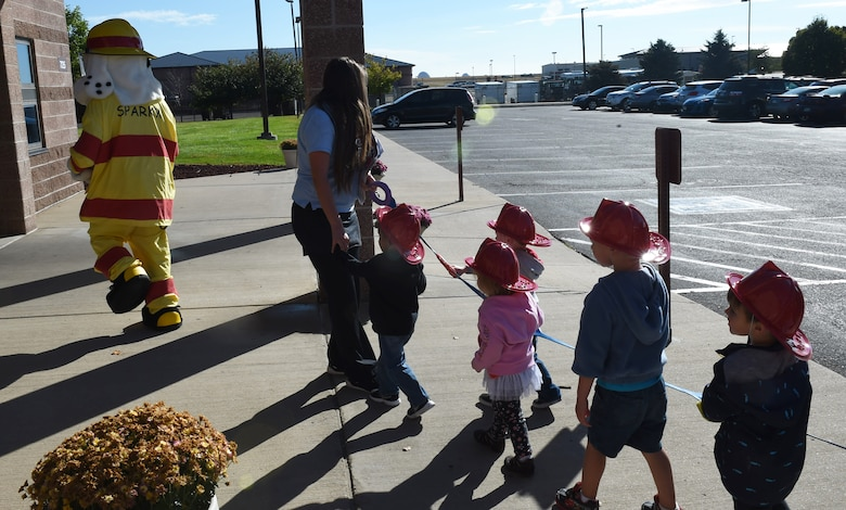 Children from the Crested Butte Child Development Center march behind Sparky the Fire Dog Oct. 7, 2015, on Buckley Air Force Base, Colo. Sparky was part of a visit from the Buckley Fire Department to both CDCs on base to spread the word about Fire Prevention Week. The fire department also brought fire trucks for the children to look at, along with plastic fire helmets and coloring books for them to take home. (U.S. Air Force photo by Airman 1st Class Samantha Meadors/Released)