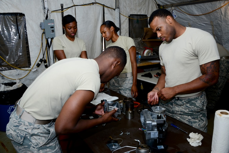 U.S. Airmen from the 355th Force Support Squadron work on reassembling Babington Airtronic burners at Davis-Monthan Air Force Base, Ariz., Sept. 30, 2015. Airmen from D-M, Luke AFB, Ariz., and Nellis AFB, Nev., attended the expeditionary kitchen training. The training was dedicated to FSS Airmen learning how to operate, repair and maintain equipment in a Single Pallet Expeditionary Kitchen. (U.S. Air Force photo by Airman 1st Class Mya M. Crosby/Released)