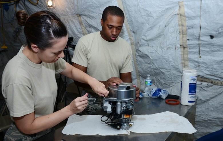 U.S. Air Force Staff Sgt. Ayala Angulo, 355th Force Support Squadron unit deployment manager, and 2nd Lt. Allante Staten, 355th FSS officer in charge of readiness, fix a Babington Airtronic burner during an expeditionary kitchen training at Davis-Monthan Air Force Base, Ariz., Sept. 30, 2015. The training was held at Desert Lighting City, D-M's training ground that mirrors a deployed location.  (U.S. Air Force photo by Airman 1st Class Mya M. Crosby/Released)
