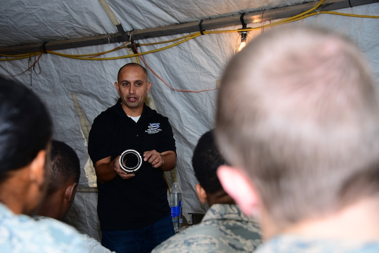 Ramiro Andrade, Babington Technology engineer, lectures on how to properly take apart a Babington Airtronic burner to 355th Force Support Squadron Airmen at Davis-Monthan Air Force Base, Ariz., Sept. 30, 2015. Andrade came to D-M to teach the Airmen how to operate, repair and maintain equipment that they would use in a deployed environment. (U.S. Air Force photo by Airman 1st Class Mya M. Crosby/Released)