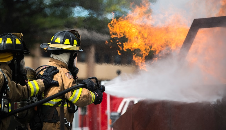 Airman 1st Class Austyn Helgeson and Senior Airman Scott Burdick, 11th Wing Civil Engineer firefighters, put out a fire during a live fire exercise at Joint Base Andrews, Md., Oct. 7, 2015. The exercise was part of the fire prevention week on JBA. (U.S Air Force photo by Airman 1st Class Philip Bryant/Released)