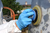 Senior Airman Carlos Colon, 509th Maintenance Squadron low observable technician, sands a Minuteman II Missile static display at Whiteman Air Force Base, Mo., Sept. 1, 2015. As part of the restoration process, the missile was sanded, primed and painted. (U.S. Air Force photo by Airman 1st Class Michaela R. Slanchik/Released)
