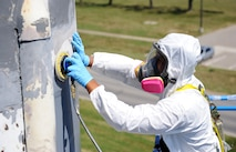 Senior Airman Carlos Colon, 509th Maintenance Squadron low observable technician, sands a Minuteman II Missile static display at Whiteman Air Force Base, Mo., Aug. 21, 2015. The missile was sanded, primed and then painted as part of the restoration process. (U.S. Air Force photo by Airman 1st Class Michaela R. Slanchik/Released)