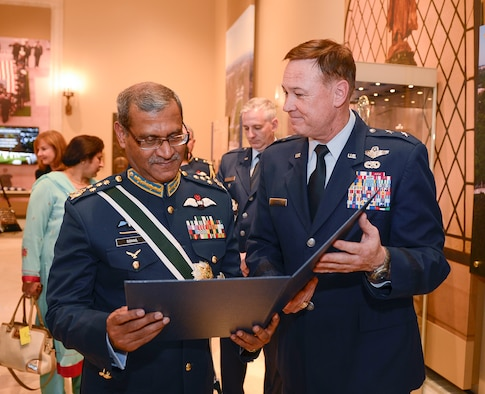 Air Chief Marshal Sohail Aman, Chief of Air Staff of the Pakistan Air Force, is presented a memento by Air Force District of Washington Commander Maj. Gen. Darryl Burke while visiting the Tomb of the Unknown Soldier for a wreath laying ceremony at Arlington National Cemetery on Oct. 6, 2015. Distinguished visitors commonly pay formal respects to the sacrifice of America's veterans in foreign wars by placing a wreath before the Tomb. The Air Force District of Washington brings air, space and cyberspace capabilities to the joint team protecting the nation's capital, and supports local personnel and those serving worldwide. (Photo/ Andy Morataya)
