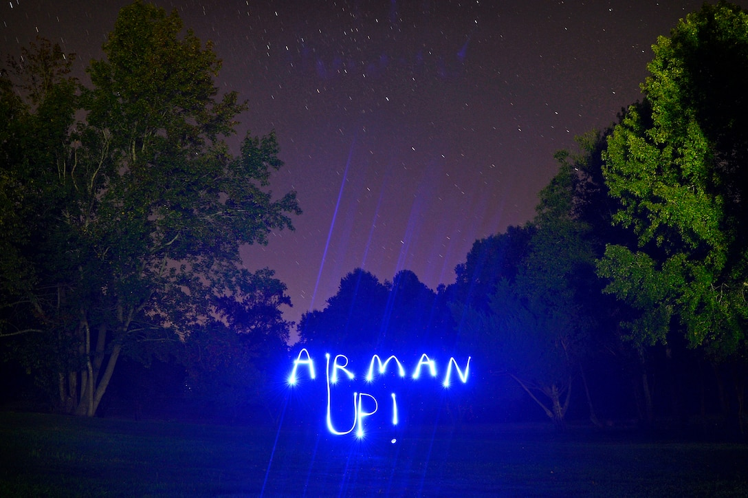 "The words ""Airman Up!"" illuminate the night at Shaw Air Force Base, S.C., Oct. 7, 2015. The phrase, created by Col. Stephen Jost, 20th Fighter Wing commander, is meant to challenge and empower Airmen to improve themselves to be better today than they were yesterday.  (U.S. Air Force photo by Senior Airman Jensen Stidham/Released)"