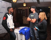 Neil Magny, currently ranked 12th in the Ultimate Fighting Championship's welterweight division, talks with Paul Loede, 55th Contracting Squadron contract administrator, and his wife, Trisha, 55th Force Support Squadron community service flight chief, at Fight Night Oct. 3, 2015, at the Patriot Club, Offutt Air Force Base, Neb. Magny met with Team Offutt personnel and joined them as they watched UFC 192. (U.S. Air Force photo by D.P. Heard/Released)