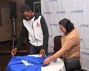 Sally Truhitte, Joint Base San Antonio business operations specialist, helps Neil Magny, currently ranked 12th in the Ultimate Fighting Championship's welterweight division, fold T-shirts that were given out to Team Offutt personnel during Fight Night Oct. 3, 2015, at the Patriot Club, Offutt Air Force Base, Neb. Offutt was one of just three bases to host a UFC fighter for UFC 192. (U.S. Air Force photo by D.P. Heard/Released)