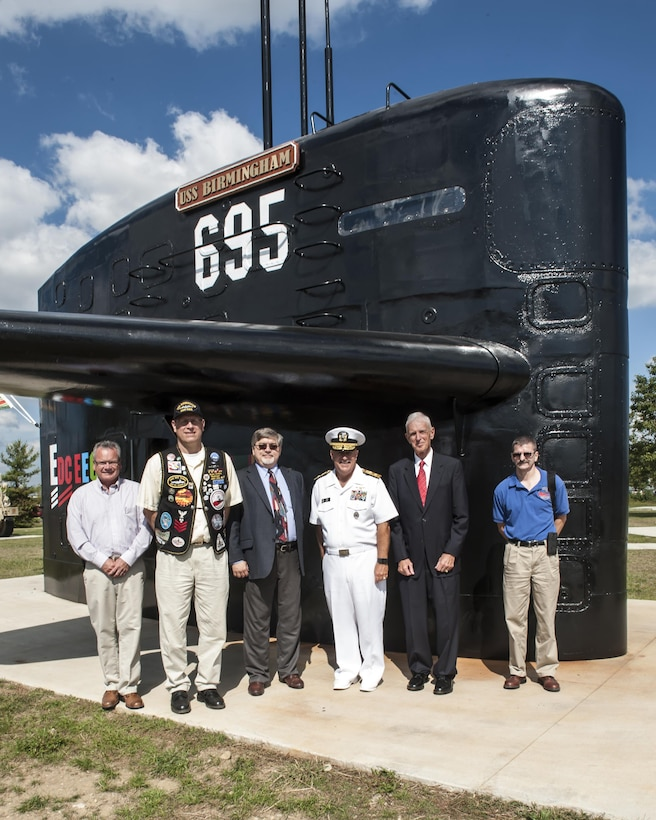Former members of the USS Birmingham submarine stand next to the ships' sail with Rear Adm. John King, DLA Land and Maritime commander, Sept. 23 after the ribbon cutting ceremony to open the brand new Mission Park on Defense Supply Center Columbus. A fitness trail links land and sea vehicles, weapons systems and historic displays that reflect DSCC's contributions to the nation's defense since 1918 at the park.