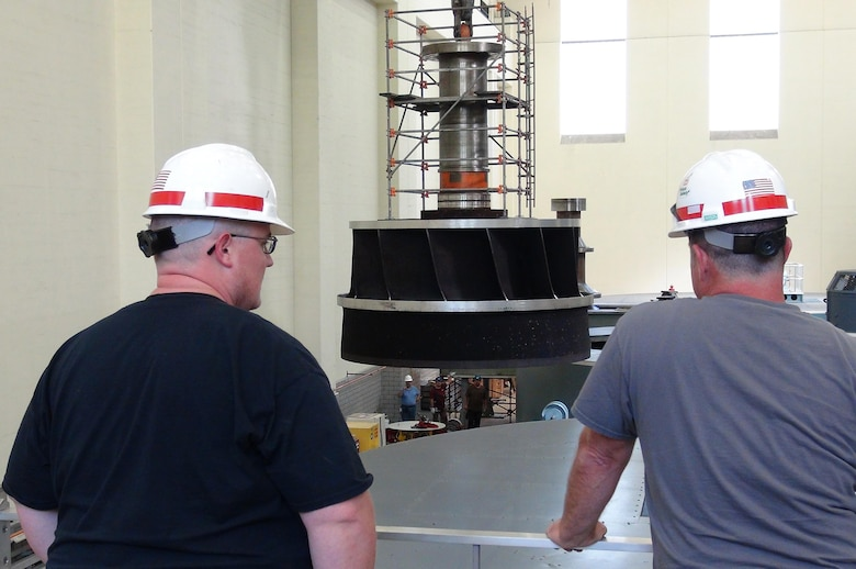 Several Corps of Engineers employees watch as work crews lift the turbine runner out of hydropower unit two in the power house at Center Hill Dam Oct. 7, 2015. The U.S. Army Corps of Engineers Nashville District is rehabbing all three units at the dam.
