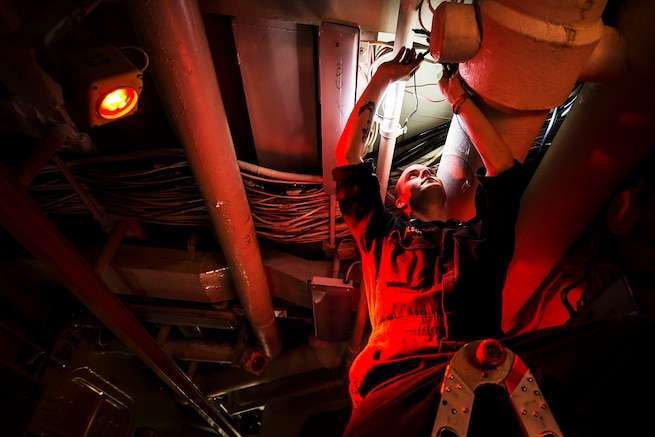 U.S. Navy Petty Officer 2nd Class Adam Wilson rewires a light fixture in a passageway aboard the USS Essex in the Arabian Gulf, Oct. 2, 2015. The Essex is supporting security efforts in the U.S. 5th Fleet area of responsibility. U.S. Navy photo by Petty Officer Class 2nd Class Huey D. Younger Jr.