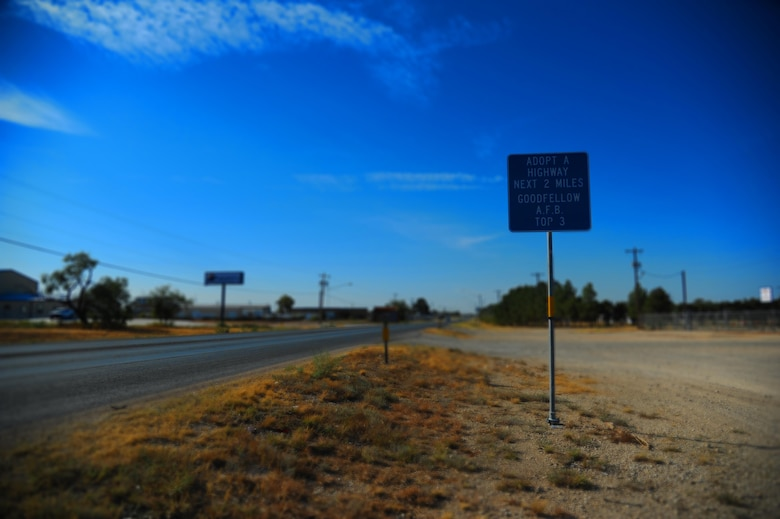 An Adopt-a-Highway sign sits on Christoval Road, a road in San Angelo, Texas, that the Goodfellow Air Force Base Top 3 organization has adopted. Goodfellow has kept the San Angelo community clean by adopting highways since 2007. (U.S. Air Force illustration by Airman Caelynn Ferguson/Released)