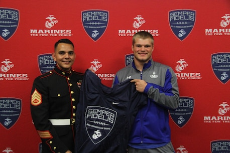 Staff Sergeant Juan C. Gomez, a canvassing recruiter with Recruiting Substation Sarasota, presents Joel Dublanko, an outside linebacker for IMG Academy, with his Semper Fidelis All American Bowl jersey Oct 7, 2015. Dublanko said he would like to thank his family for supporting him throughout his football career and that he looks forward to spending a week with the Marines in California.