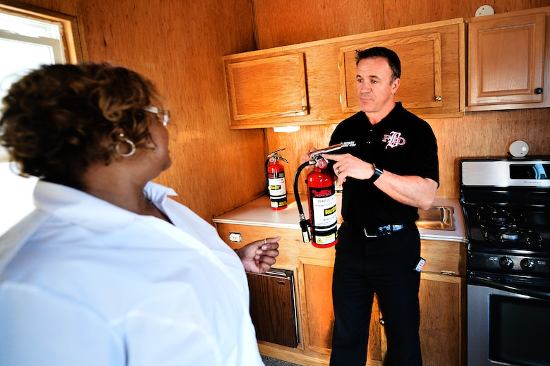 David Herman, Buckley Fire Department fire chief, demonstrates how to properly use a fire extinguisher Oct. 8, 2015, on Buckley Air Force Base, Colo. The fire department offered fire extinguisher training, which involved pointing a fake fire extinguisher at simulated house fires, to Team Buckley members as part of Fire Prevention Week. (U.S. Air Force photo by Staff Sgt. Darren Scott/Released)