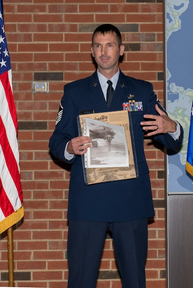 Master Sgt. Michael Tucker, Cyber Space Support Squadron NCOIC of Cyber Operation Requirements, shows a copy of the Scott Broadcaster that his grandfather was on the cover of in 1945. Michael Tucker's grandfather was at Scott Field during the end of his service in World War 2. (U.S. Air Force Photo by Senior Airman Megan Friedl)