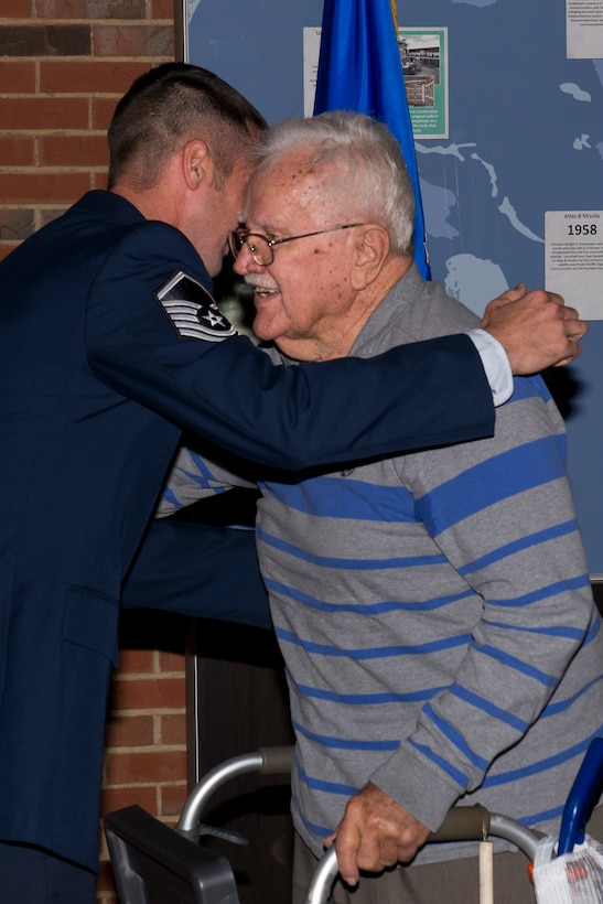 Master Sgt. Michael Tucker, Cyber Space Support Squadron NCOIC of Cyber Operation Requirements, hugs his grandfather, Robert Tucker Sr. right after he received his Master Sgt. stripes. Michael Tucker's grandfather was very influential to him in his life and career. (U.S. Air Force Photo by Senior Airman Megan Friedl)