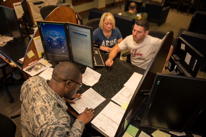 Airman Christopher Tillman, 628th Comptroller Squadron financial systems technician, helps SSgt. Rob MacPeek, 628th Logistics Readiness Squadron vehicle maintenance operator and Candace MacPeek file paperwork in the finance office on Joint Base Charleston – Air Base, S.C., Oct. 7, 2015. MacPeek and his wife, Candace, were updating their marital status.