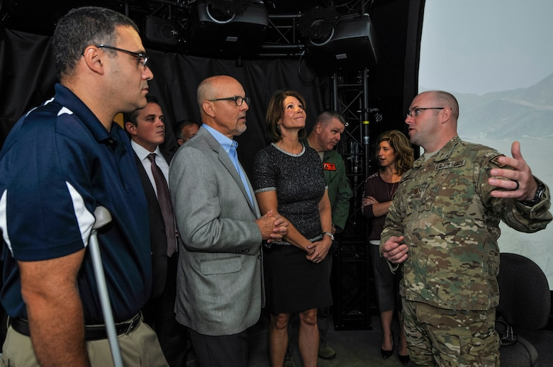 U.S. Air Force Master Sgt. Eric M. Dubois, operations superintendent at the 169th Air Support Operations Squadron, Illinois Air National Guard, explains to, from left, state Rep. Michael Unes, R-East Peoria., state Sen. David Koehler, D-Peoria., and U.S. Rep. Cheri Bustos, D-Ill., how the Air National Guard Advanced Joint Terminal Attack Controller Training System works after a ribbon cutting ceremony at the 182nd Airlift Wing in Peoria, Ill., Oct. 5, 2015. Peoria's 169th Air Support Operations Squadron TACPs teamed up with the QuantaDyn Corporation to help create the AAJTS, which is expected to potentially save the government $95 million through fiscal year 2018 by reducing the cost of qualification and continuation training by 48 percent. (U.S. Air National Guard photo by Staff Sgt. Lealan Buehrer/Released)