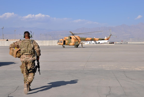 U.S. Air Force Tech. Sgt. Angel Gonzalez, C-130 maintenance supply liaison at Train, Advise, Assist Command - Air makes his way to an Afghan air force Mi-17 helicopter at Bagram Air Field, Afghanistan, Oct. 5, 2015. Gonzalez flies from Kabul to Bagram multiple times a week to cut roughly 10 days off the shipping process for C-130 parts needed to maintain and sustain the Afghan air force's C-130 Hercules aircraft flying in support of Afghan army operations across the country. U.S. Air Force photo by Capt. Edith Sakura