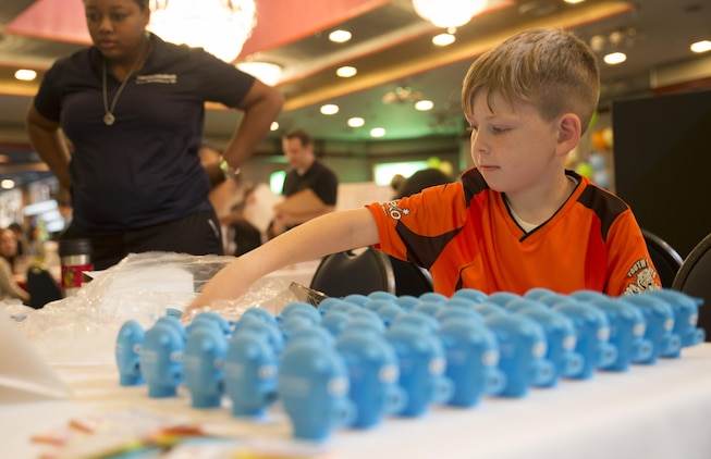 Lucas Henson, Info Expo participant, helps set up a display at the Community Bank table during the Info Expo inside the Club Iwakuni Grand Ballroom aboard Marine Corps Air Station Iwakuni, Japan, Sept. 12, 2015. The Info Expo continues to grow each year, with more and more local Japanese vendors joining, making it easier for station residents to access local travel and services information as well as providing an opening for the Japanese community to experience the American culture.