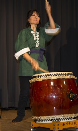 "Dr. Suzanne Landrum, principal of Matthew C. Perry Elementary School, plays the drums with a local drum group, ""Marifu Daiko"", during the Info Expo inside the Club Iwakuni Grand Ballroom aboard Marine Corps Air Station Iwakuni, Japan, Sept. 12, 2015. The group includes station residents and local Japanese drummers. The Info Expo provided an opportunity for station residents to familiarize themselves with services offered on and off base as well as travel, shopping, and cultural experiences available."