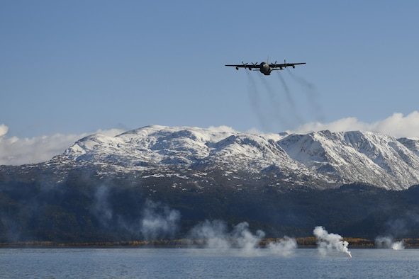 "An HC-130 Hercules from the 211th Rescue Squadron drops signal flares in the inner bay of Homer, Alaska, as part of rescue water training Sept. 30, 2015. The 210th, 211th and 212th Rescue Squadrons of the Alaska Air Guard's 176th Wing trained on water rescue tactics Sept. 30 to Oct. 1. The wing's ""rescue triad"" performed both day and night missions including personnel jumps and cargo drops on a moving target, flying night water operations, visual search for casualties and drop zone control for safety and situation management. (U.S. Air National Guard photo/Tech. Sgt. N. Alicia Halla)"