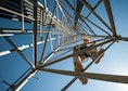 Senior Airman James Vrtis, a 57th Operations Support Squadron airfield systems technician, descends a ground-to-air radio tower on Nellis Air Force Base, Nev., Oct. 6, 2015. Airfield systems specialists must periodically perform preventative maintenance inspections on ground-to-air radio towers, which stand as tall as 180 feet. (U.S. Air Force photo/Staff Sgt. Siuta B. Ika)