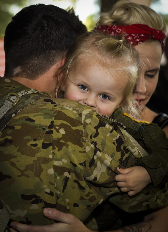 Tech Sgt. Andrew Melton, a 4th Special Operations Squadron special missions aviator, embraces his loved ones after returning home from a deployment during Operation Homecoming at the Deployment Control Center on Hurlburt Field, Fla., Oct. 7, 2015. Families and friends of 59 air commandos gathered to welcome home their loved ones from a deployment overseas. (U.S. Air Force photo/Airman Kai White)