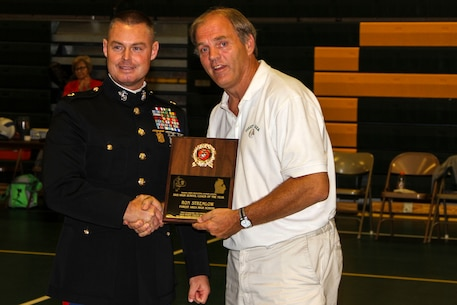 Maj. Christopher L. Buck, Recruiting Station Lansing commanding officer, left, presents Ron Stremlow, Forest Area High School coach, with the Recruiting Station Lansing High School Coach of the Year Award inside the Forest Area High School gymnasium, Oct. 8, 2015. Ron Stremlow coached volleyball, girls and boys soccer and basketball, track, football, and middle school basketball. Each year, RS Lansing solicits nominations from high schools throughout Michigan and recognizes one male and one female coach that exemplifies the Marine Corps values of honor, courage and commitment.