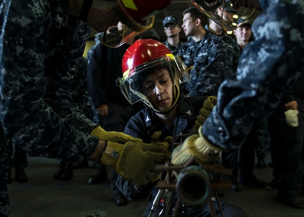 U.S. Navy Petty Officer 3rd Class Berney Jarosz practices pipe-patching during a general quarters drill in the hangar bay of the USS Ronald Reagan in Yokosuka, Japan, Oct. 8, 2015. Jarosz is a machinist's mate. U.S. Navy photo by Petty Officer 3rd Class Nathan Burke