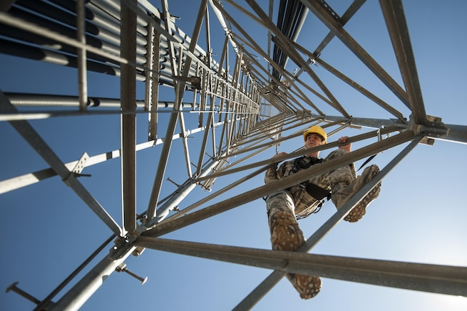 Air Force Senior Airman James Vrtis descends a ground-to-air radio tower at the airfield systems maintenance compound on Nellis Air Force Base, Nev., Oct. 6, 2015. Vrtis is an airfield systems technician with the 57th Operations Support Squadron. U.S. Air Force photo by Staff Sgt. Siuta B. Ika