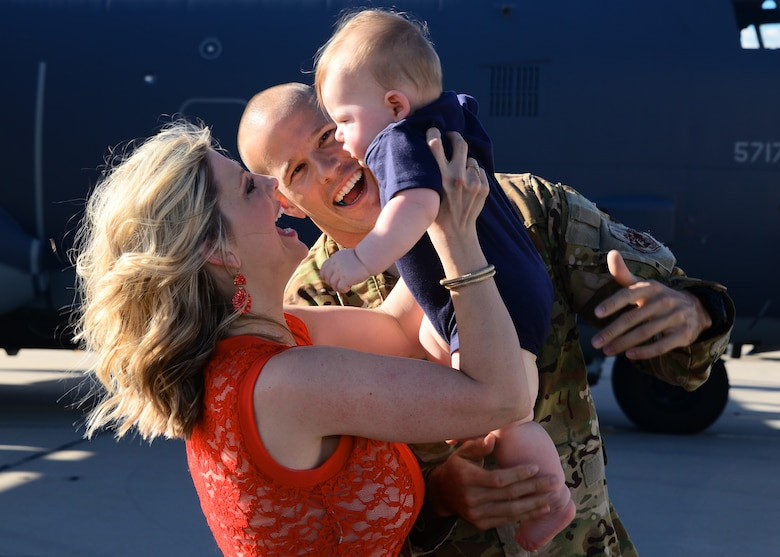 U.S. Air Force Capt. Nick Pettit, 563rd Operation Support Squadron, embraces his family on the flightline at Davis-Monthan Air Force Base, Ariz., Oct. 9, 2015. Two HC-130J Combat King II's and 25 Airmen returned from a 4-month deployment to Southwest Asia. (U.S. Air Force photo by Airman 1st Class Mya M. Crosby/Released)