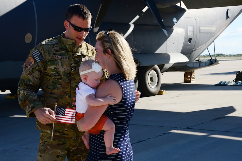 U.S. Air Force Capt. Ronald Maxfield, 79th Rescue Squadron combat systems officer, embraces his family on the flightline at Davis-Monthan Air Force Base, Ariz., Oct. 9, 2015. Two HC-130J Combat King IIs and 25 Airmen returned from a 4-month deployment to Southwest Asia. (U.S. Air Force photo by Airman 1st Class Mya M. Crosby/Released)