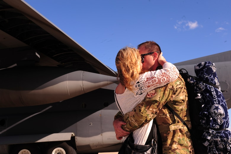 U.S. Air Force Staff Sgt. Tim Fitzpatrick, 563rd Operations Support Squadron loadmaster, embraces his wife, Laura Fitzpatrick, on the flightline at Davis-Monthan Air Force Base, Ariz., Oct. 9, 2015. Two HC-130J Combat King II's and 25 Airmen returned from a 4-month deployment to Southwest Asia. (U.S. Air Force photo by Airman Basic Nathan H. Barbour/Released)