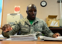 U.S. Air Force Senior Airman Devarius Dawkins, a 354th Force Support Squadron readiness and plans journeyman, flips through the vehicle control officer (VCO) binder Oct. 9, 2015, at Eielson Air Force Base, Alaska. Dawkins uses this binder to keep track of the paperwork that goes with the VCO program.  (U.S. Air Force photo by Airman 1st Class Cassandra Whitman/Released)