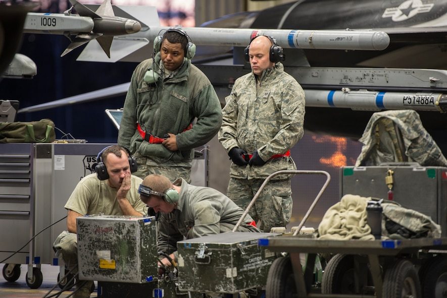"""Members of the 354th Aircraft Maintenance Squadron (AMXS) troubleshoot an F-16 Fighting Falcon assigned to the 18th Aggressor Squadron at Eielson Air Force Base, Alaska, Oct. 8, 2015. The 354th AMXS created a program called """"cut training"""" to cross utilize Airmen to fill undermanned crew chief positions. Lawrence was the first Airman to complete the program. (U.S. Air Force photo by Staff Sgt. Joshua Turner/Released)"""