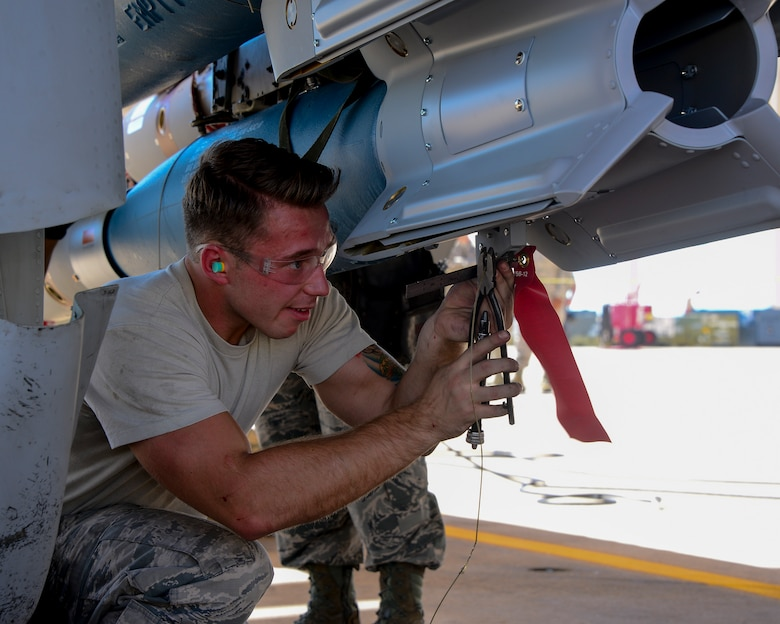 U.S. Air Force Airman 1st Class Christopher Sisk, 354th Aircraft Maintenance Unit load crew team member, wires a control computer group of a Guided Bomb Unit-12 Paveway II during a load crew of the quarter contest at Davis-Monthan Air Force Base, Ariz., Oct. 2, 2015. The selected Airmen for the contest were hand-picked from their unit leadership to compete. (U.S. Air Force photo by Airman 1st Class Mya M. Crosby/Released)