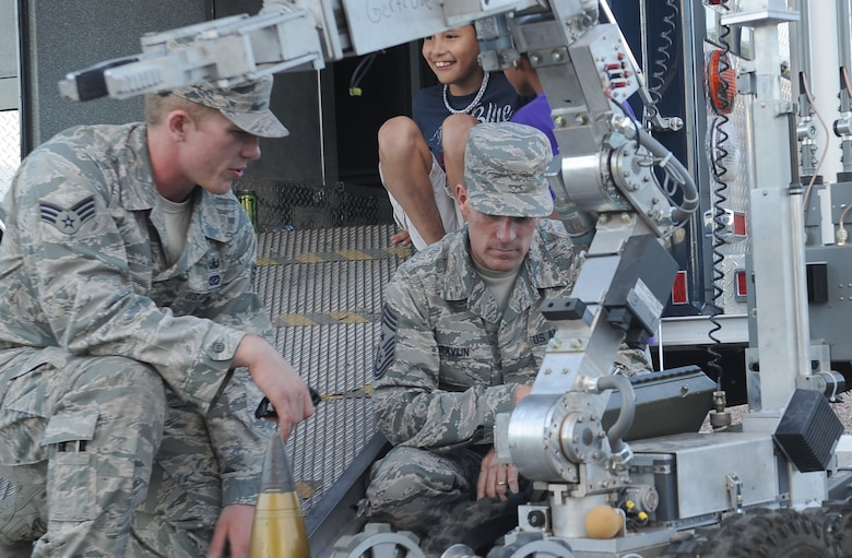 "U.S. Air Force Senior Airman Mathew Shoup, 355th Civil Engineer Squadron explosive ordnance disposal technician, explains the capabilities of ""Gertrude,"" a F6A robot, to Chief Master Sgt. Jeremy Ravlin, 355th Fighter Wing command chief, during a National Night Out event held at Davis-Monthan Air Force Base, Ariz., Oct. 7, 2015. This is the ninth year that D-M has participated in the event however, the event has been happening for 34 years around the world. Neighbors celebrate in 16,124 communities from all fifty states, U.S. Territories, Canadian cities, and military bases worldwide. While most communities celebrate National Night Out on the first Tuesday in August, Soaring Heights holds its event during October due to Tucson's extreme heat in August. (U.S. Air Force photo by Senior Airman Cheyenne A. Powers/Released)"