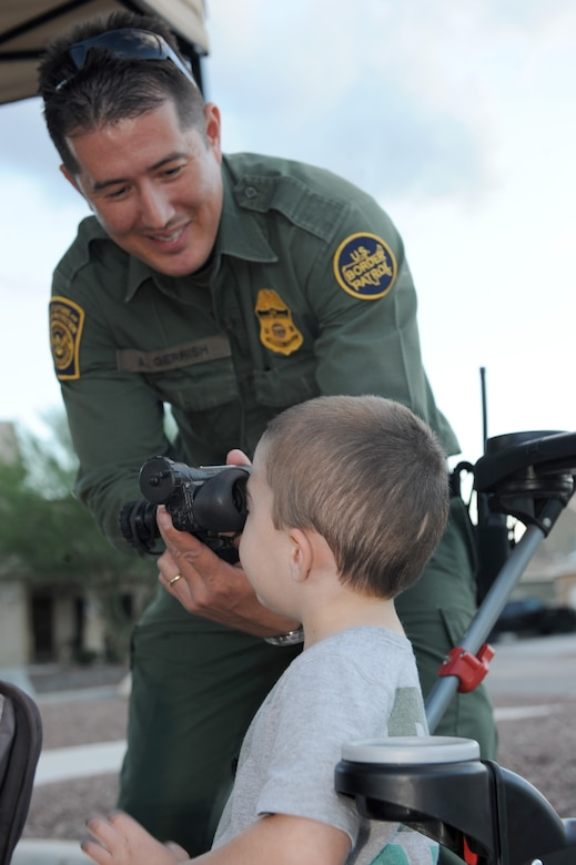 U.S. Border Patrol agent Arick Gerrish shows the son of Staff Sgt. Corey Strohmeyer, 355th Logistics Readiness Squadron noncommissioned officer in charge of fire truck maintenance night vision goggles during a National Night Out event held at Davis-Monthan Air Force base, Ariz., Oct. 7, 2015. The event gave residents of Soaring Heights and anyone with base access an opportunity to meet and learn about D-M's first responders and gain valuable information from local emergency services. (U.S. Air Force photo by Senior Airman Cheyenne A. Powers/Released)