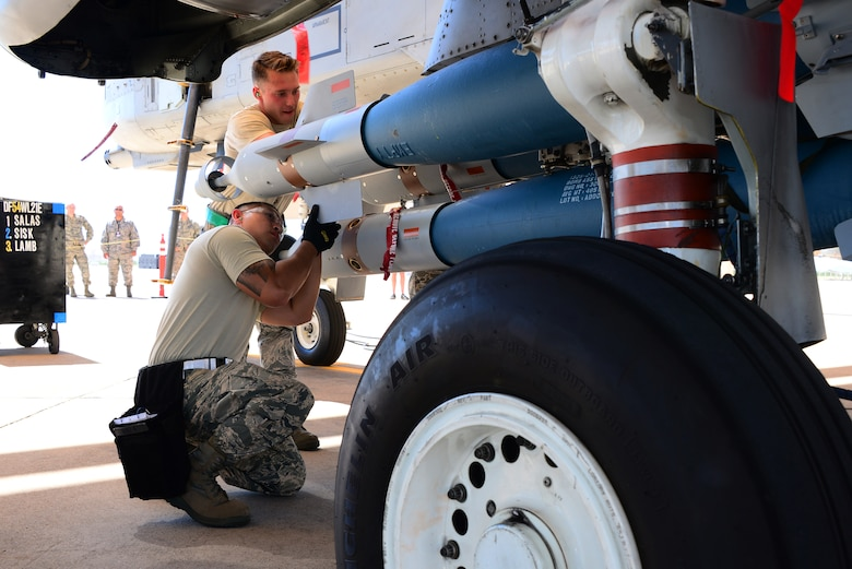 Airmen assigned to the 354th Aircraft Maintenance Unit, work together to load a Guided Bomb Unit-12 Pavement II onto an A-10 Thunderbolt II during a load crew of the quarter contest at Davis-Monthan Air Force Base, Ariz., Oct. 2, 2015. Load crew from the 354th AMU and the 924th Aircraft Maintenance Squadron competed against each other for the contest. (U.S. Air Force photo by Airman 1st Class Mya M. Crosby/Released)