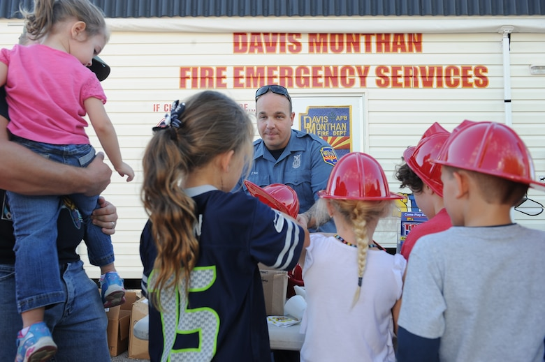 U.S. Air Force Jason Rice, 355th Civil Engineering Squadron Fire and Emergencies Services unit captain, passes out helmets and pamphlets to local children during a National Night Out event at Davis-Monthan Air Force Base, Ariz., Oct. 7, 2015. The event is intended to educate the public about crime and drug prevention as well as strengthen neighborhood spirit and security-organization. Rice gave children and parents different items that would help teach them this in a fun way. (U.S. Air Force photo by Senior Airman Cheyenne A. Powers/Released)