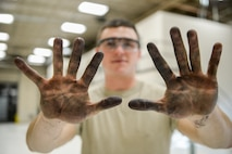 U.S. Air Force Senior Airman Cody Bowman, a 354th Maintenance Squadron aerospace propulsion journeyman, shows oil and dirt on his hands after working on an F110-GE-100C jet engine Oct. 8, 2015, during an engine rebuild in the engine shop at Eielson Air Force Base, Alaska. Bowman disassembled engine components for inspection and replacement, a process which can take several months and hundreds of man hours. (U.S. Air Force photo by Senior Airman Peter Reft/Released)