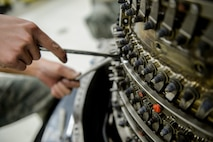U.S. Air Force Airman 1st Class Brandon Trang, a 354th Maintenance Squadron aerospace propulsion apprentice, extracts bolts from an F110-GE-100C jet engine Oct. 8, 2015, in the engine shop at Eielson Air Force Base, Alaska. Trang inspected engine components for damage and wear. (U.S. Air Force photo by Senior Airman Peter Reft/Released)